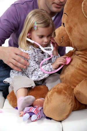 Young girl listening to her teddy's heartbeat photo
