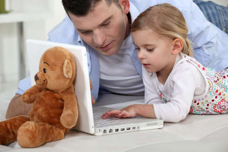 father teaching daughter: Young girl playing with her fathers laptop
