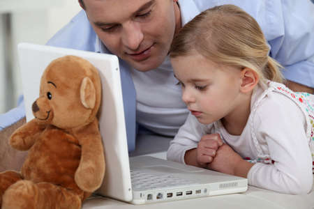 Little girl and her dad using the laptop photo