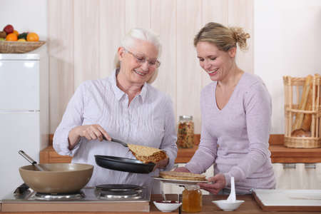 honey blonde: Mother and daughter cooking crepes
