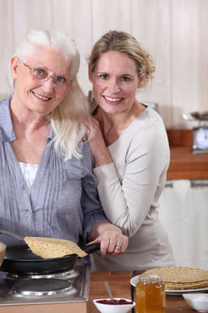 Mother and daughter cooking crepes together photo