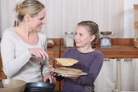 Little girl and mother about to eat pancakes for breakfast photo