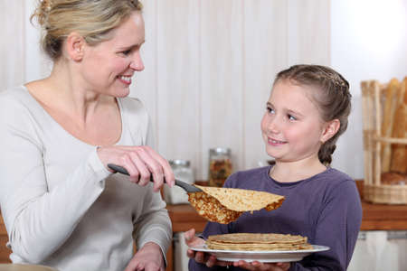 A mother cooking crepes with her daughter. Stock Photo - 14213536