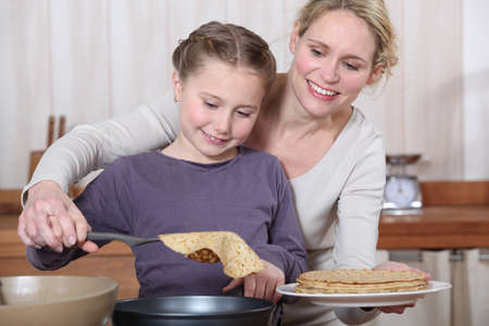 Mother and daughter making crepes together photo