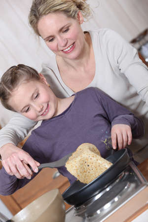 Mother and daughter cooking pancakes photo
