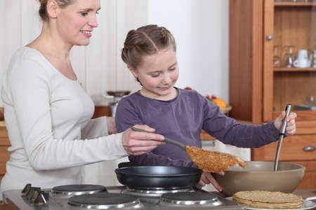Woman teaching her daughter how to make crepes photo