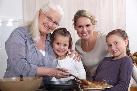 Mother, grandmother, and girls cooking pancakes photo
