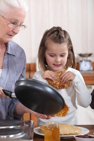 farinaceous: Grandmother and granddaughter making pancakes