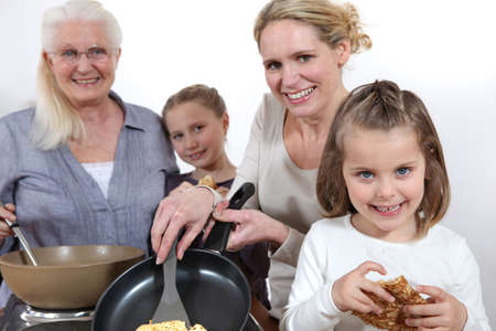 Three generations cooking pancakes photo