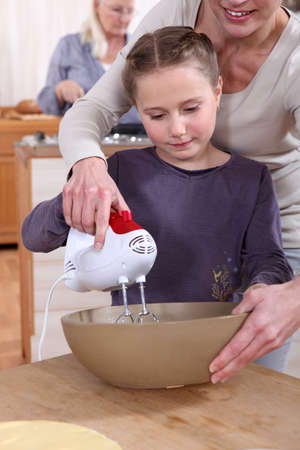 Woman helping her daughter use a hand mixer photo