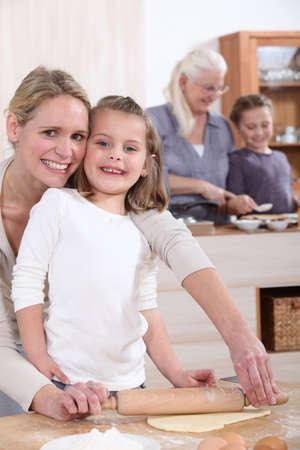Young girl baking with her mother photo