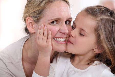 little girl kissing woman photo