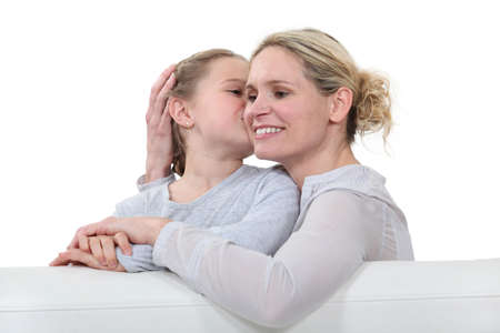 undisturbed: Mother and daughter sat on sofa