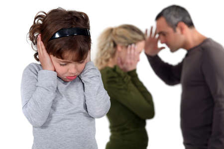 tantrum: Daughter stood with arguing parents Stock Photo