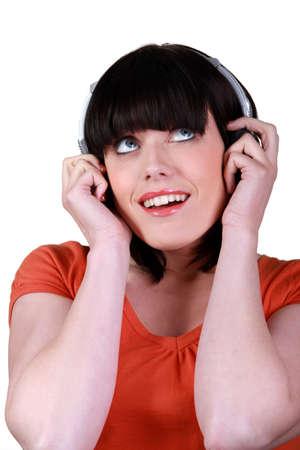 Brunette listening to music through headphones photo