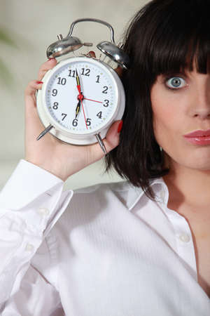 Woman with tousled hair holding alarm clock photo