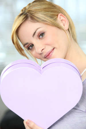Woman holding heart-shaped box photo