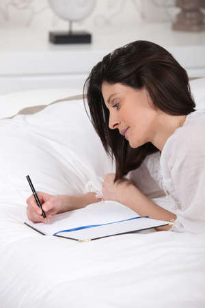 poem: Woman laid on her bed writing on a notebook Stock Photo