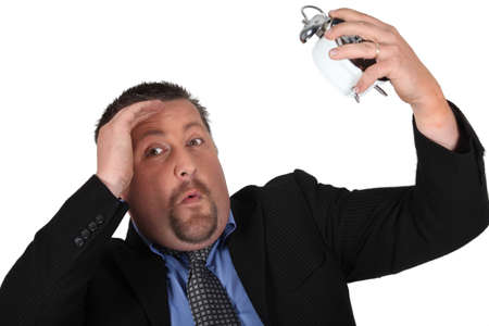 anguished: Panicked man in suit watching alarm clock
