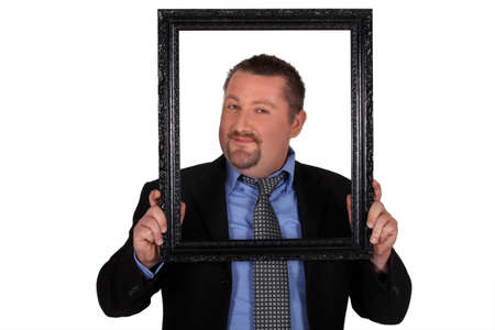 Businessman carrying frame in front of his face photo