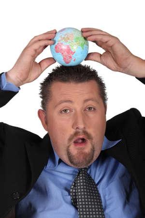 online internet presence: Businessman balancing a globe on his head