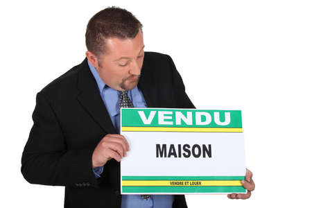 Estate agent holding sold sign photo