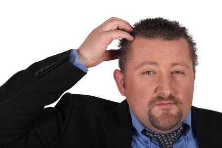 Businessman scratching his head photo