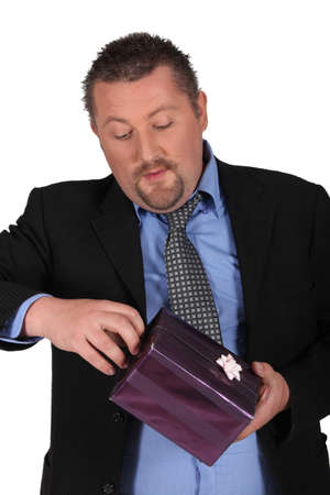 man with a goatee: Man opening a present Stock Photo