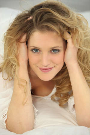 a blonde woman on a bed touching her hair Stock Photo - 14214636