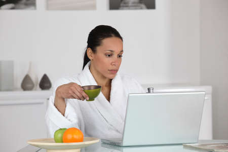 replying: Woman having coffee at home in dressing gown