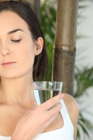 Woman drinking a glass of water photo