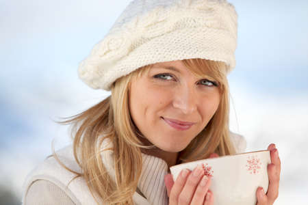 Woman keeping warn by drinking bowl of hot chocolate Stock Photo
