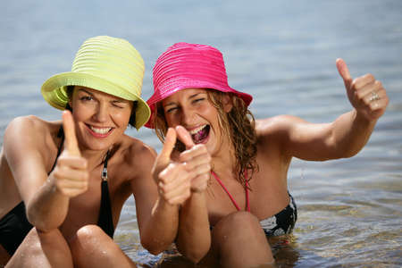 ok sign: Two women at the beach giving the thumbs-up