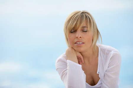 unwinding: Woman unwinding alone at the seaside Stock Photo