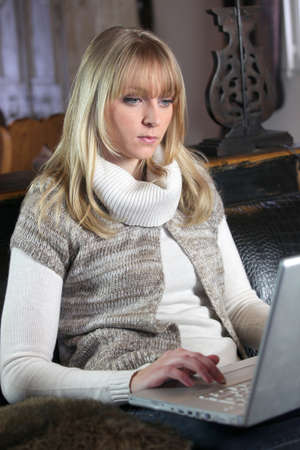 cocooning: Young woman using a laptop computer