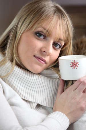 Woman drinking hot beverage to warm herself up photo