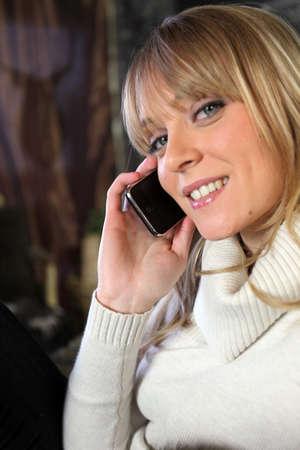 Blond woman sat on sofa calling friend Stock Photo - 14791999