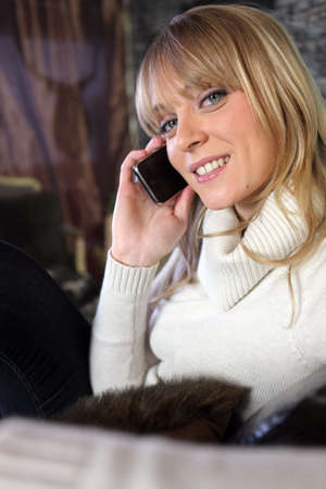 Woman in cosy jumper sat on couch making telephone call photo