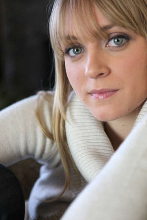 Blond woman in winter jumper sat on sofa photo