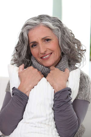 Stylish older woman holding a pillow