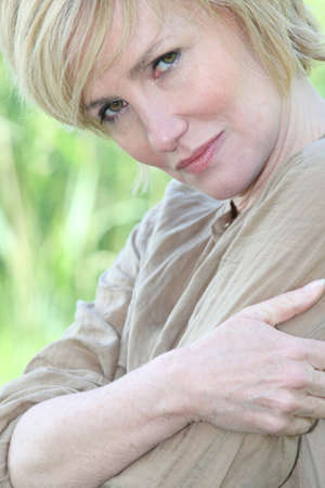 mature blonde woman is watching the camera gravely photo