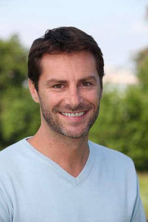 visage homme: Un portrait d'un modèle masculin dans un parc. Banque d'images
