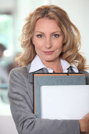 enterprising: Businesswoman holding a file folder and a laptop