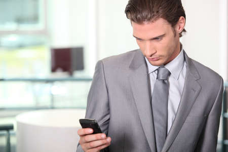 upwardly mobile: Male executive checking messages on cellphone
