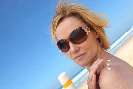 Woman at beach applying sun cream photo