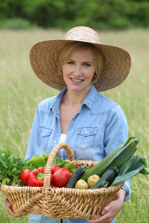 potato tree: Woman stood in field carrying basket of vegetables