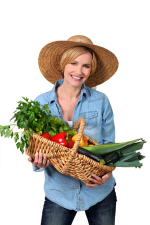 Blond carrying a basket full of vegetables. photo