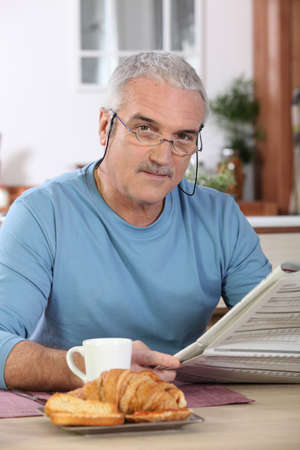 Middle-aged man reading newspaper whilst eating breakfast photo