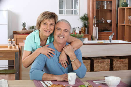 Middle-aged couple having breakfast together in kitchen photo