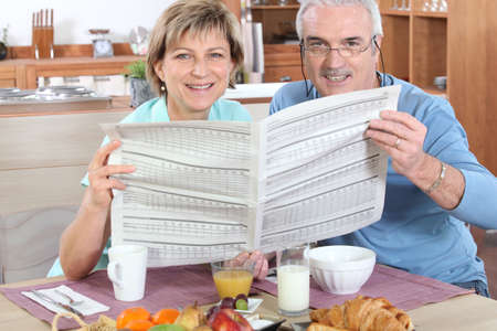 Senior couple reading newspaper photo
